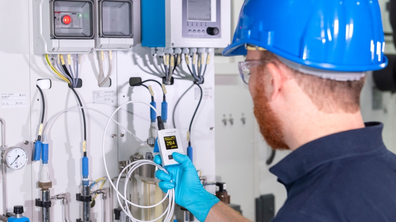 Man checking the conductivity value with CML18 at a measuring point in his production plant